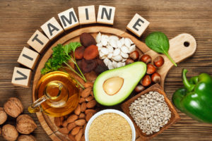 Foods rich in vitamin E such as wheat germ oil, dried wheat germ, dried apricots, hazelnuts, almonds, parsley leaves, avocado, walnuts, pumpkin seeds, sunflower seeds, spinach and green paprika on wooden table